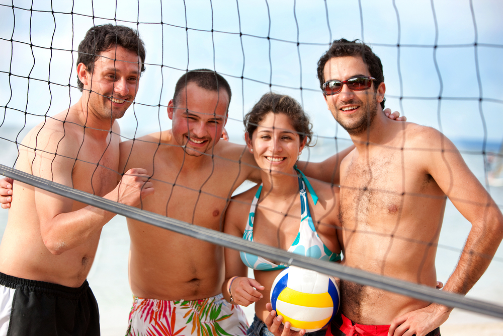 Team of friends playing volleyball at the beach